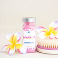 plumeria foaming bath made with goat milk on natural background with pink flowers