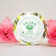 round wild azalea goat milk soap on natural background with pink flowers framing it