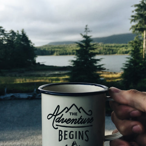 cup that says the adventure begins held in front of forest and lake