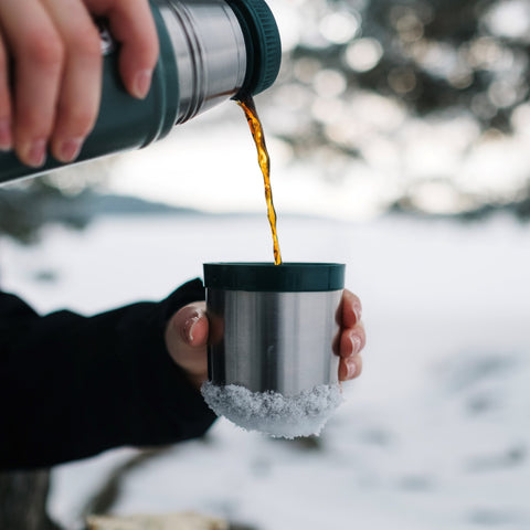 person pouring coffee from mug