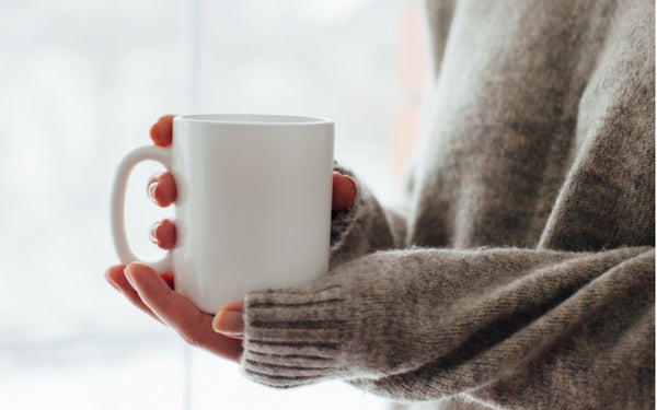 Woman in a cozy winter sweater holding a warm mug of coffee