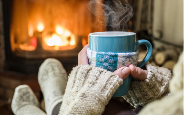 Woman drinking hot coffee by a fire at Christmas