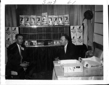 Two employees of Lowe's monitor an exhibit at a pet convention in 1961. From the photo album of Darlene Lowe. Courtesy the Edward Lowe Foundation Archives, Hagley Museum & Archives