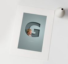 Load image into Gallery viewer, luxury print of young blond boy digitally incorporated in to a 3D paper cut out effect of the initial letter of his name and his name written in full underneath in a smart typeface