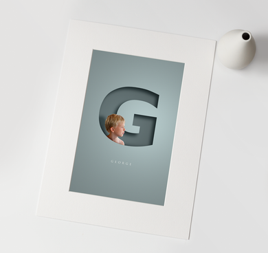 luxury print of young blond boy digitally incorporated in to a 3D paper cut out effect of the initial letter of his name and his name written in full underneath in a smart typeface