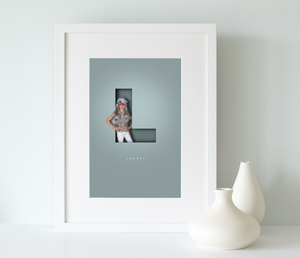 Luxury print framed in a white wood picture frame of a young girl wearing a silver wig and standing within the letter L with a 3D effect and her name written underneath in a smart serif font