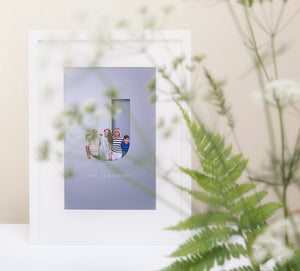 lifestyle image of family in a capital letter design in a white wood picture frame