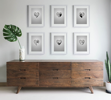 Load image into Gallery viewer, Set of black and white picture frames arranged uniformly on wall above sideboard