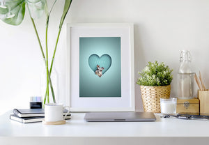 white framed picture of a cute schnauzer dog peeking out of a heart shape in a 3D paper cut out effect perched on a desk in a home office