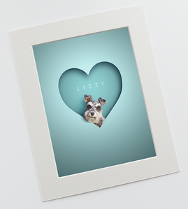 "luxurious fine art print in a 12"" x 16"" textured mount of a cute schnauzer dog head looking out of a bright blue, paper cut out effect heart shape and her name is above in a smart typeface"
