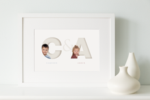 Load image into Gallery viewer, white framed picture of two children, each one sitting inside the initial letter of their name and their full name written below in a classy serif font