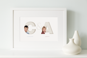 white framed picture of two children, each one sitting inside the initial letter of their name and their full name written below in a classy serif font