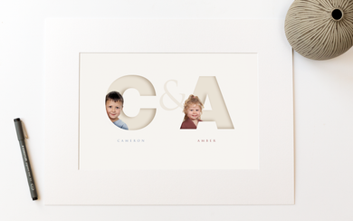 picture in photo mount of two children, each one sitting inside the initial letter of their name and their full name written below in a classy serif font