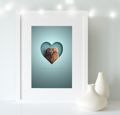 White, wooden framed picture of 2 shaggy cockapoo dogs in a cut out heart shape and their names written underneath