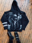 "The back of a black hooded sweatshirt featuring HR Giger's ""Satan I"" painting on the back"