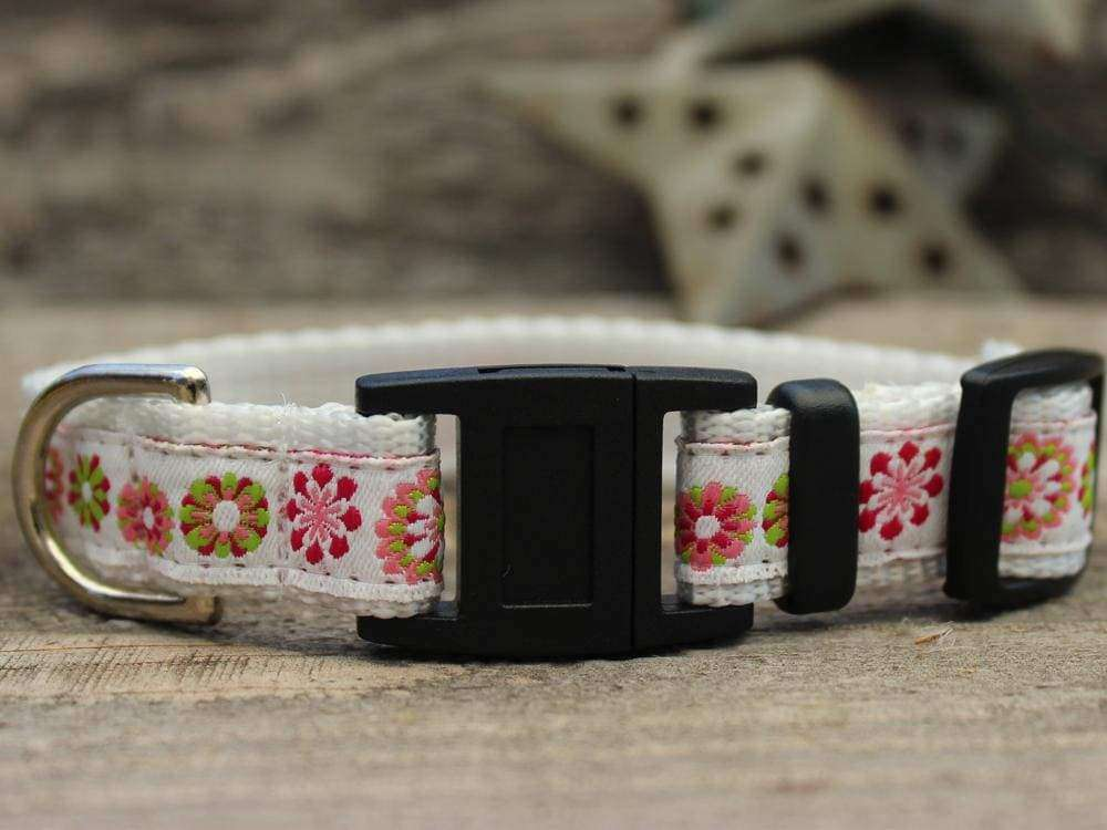 This is the Winter Garden Breakaway Buckle Cat Collar by Surf Cat. It features floral patterns set on a winter white fabric. The has breakaway buckles that pop open under eight pounds of pressure. This helps reduce choking hazards. The collar is made with soft and comfortable nylon overlaid with durable polyester ribbon. uintuple stitching at stress points provides extra strength too. So your cat gets a strong, comfortable collar.  Edit alt text