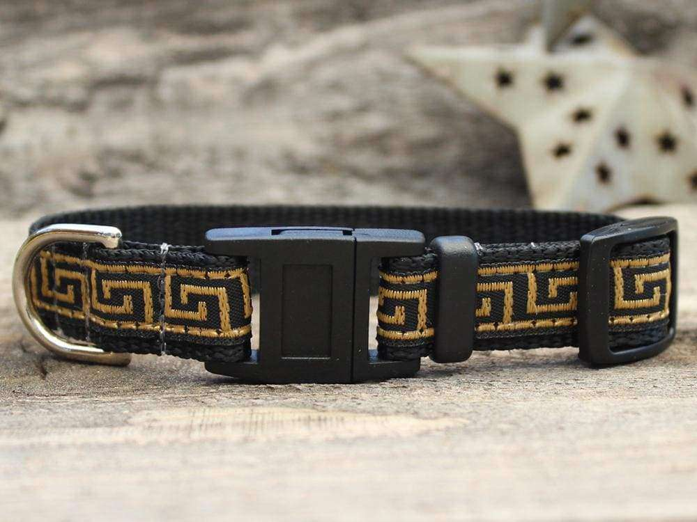This is the Caesar Break Away Cat Collar by Diva Dog and Surf Cat. The collar has a Greek geometric design, with lines creating a maze look across the collar. The lines are of golden brown hue. The collar was manufactured in the USA. It has breakaway buckles that pop open under a minimal eight pounds of pull, which helps prevent choking. The collar is made of of soft and comfortable nylon overlaid with durable polyester ribbon. The material is quintuple stitched at stress points for added strength.