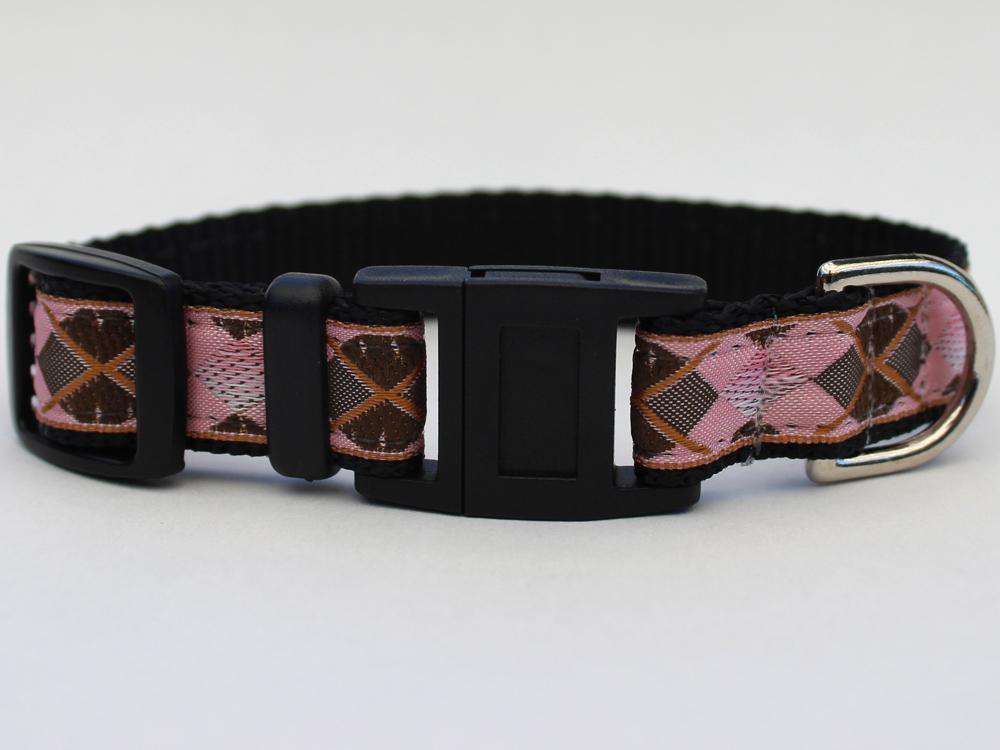 This is the Argyle Design Breakaway Buckle Cat Collar by Surf Cat. It features a pink, grey, copper, and black argyle design that resembles some golfer's clothing. The collar features  breakaway buckles that pop apart under eight pounds of pressure, which reduces the chances of choking. It's made of cozy and pliable nylon overlaid with lasting polyester ribbon. This creates comfort and a strong collar for your cat. Plus, the quintuple stitching at stress points provides crazy additional durability.