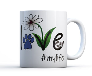 A white ceramic coffee mug with the words Love #mylife, a flower and a sleeping cat or kitten.