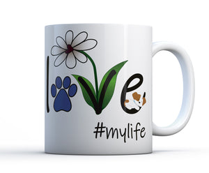 A white ceramic coffee mug with Love #mylife graphic, a flower and a sleeping dog or puppy.