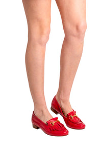 Red Italian leather loafers with fringe and gold buckle detail on model