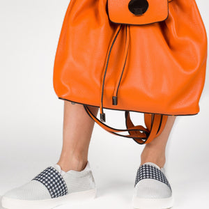 orange leather drawstring top backpack white slip on sneakers