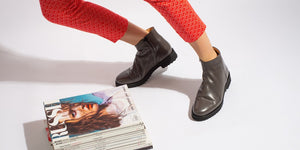 Grey Italian leather zip up ankle boot on model with magazine pile