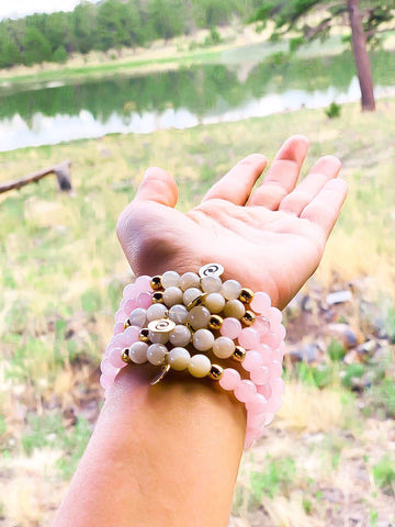 Wrist wearing a stack healing gemstone bead bracelets with rose quartz and moonstone.