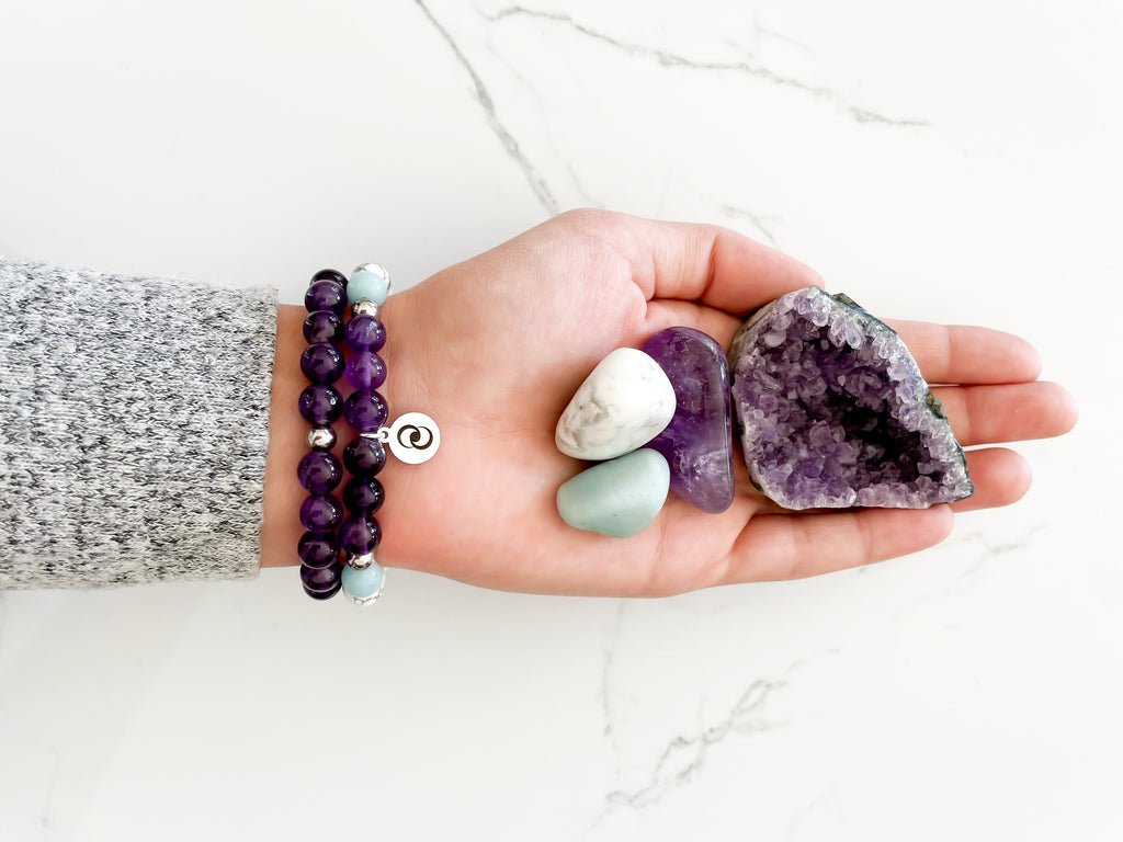 Left hand facing up wearing a health and wellness crystal bracelet stack and holding crystals.