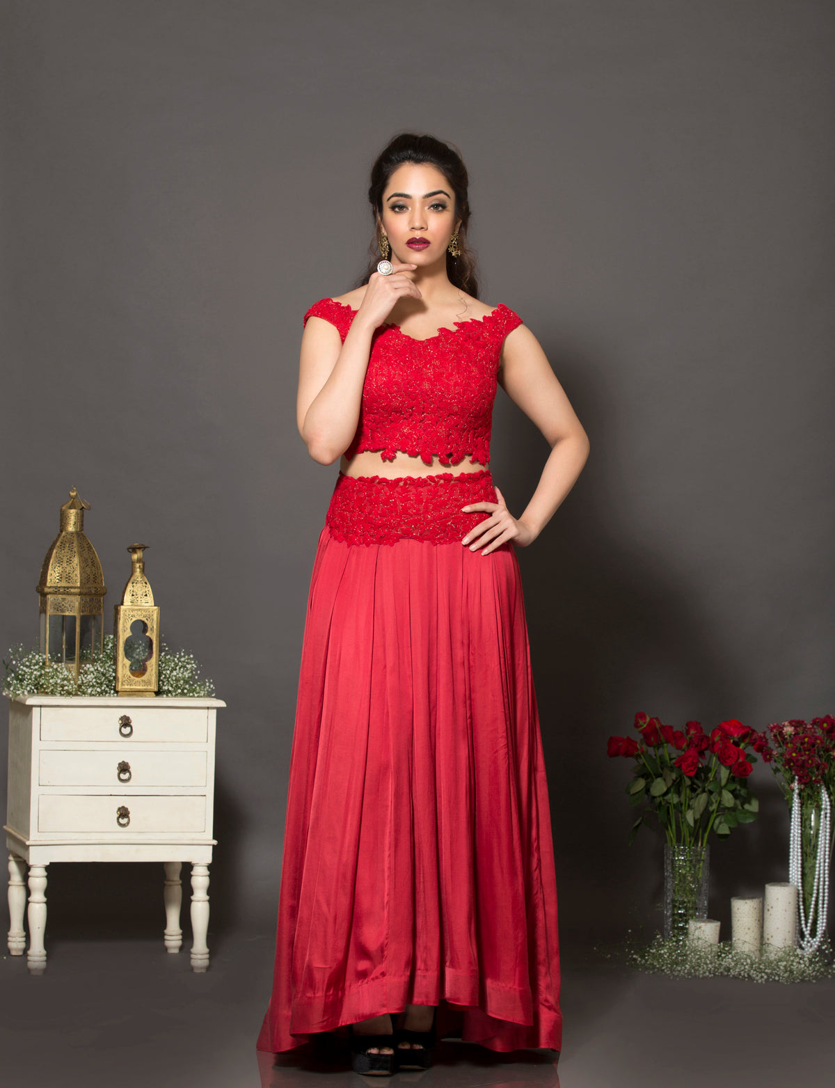 A red off-shoulder lehenga set in cotton satin that has an intricate thread work detailing all over the blouse and the belt.