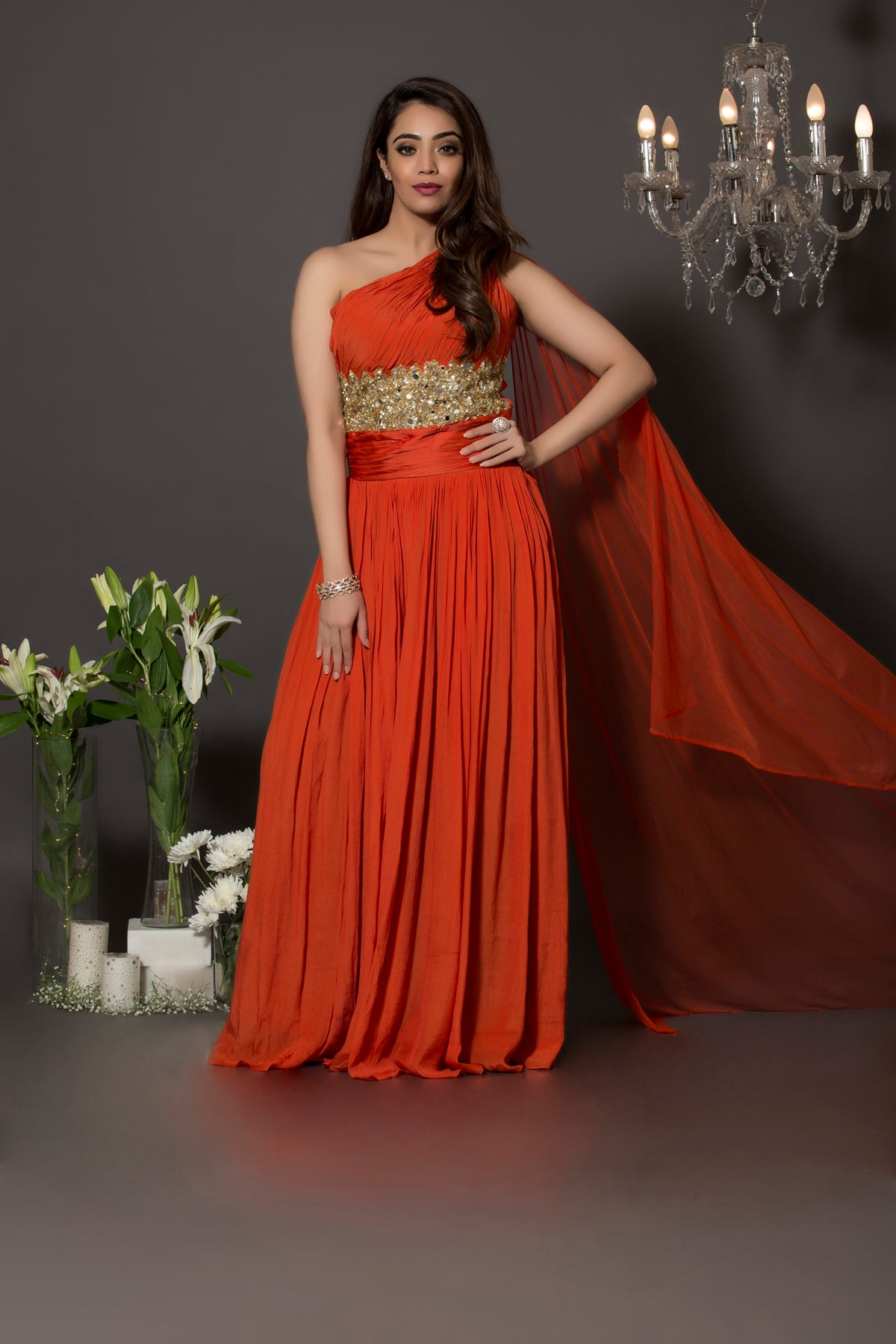 Pure crepe rust one shoulder jumpsuit with gathers on the body and sequins and mirror beautifully had crafted above the waist. This piece comes with a soft net veil attached at the shoulder.
