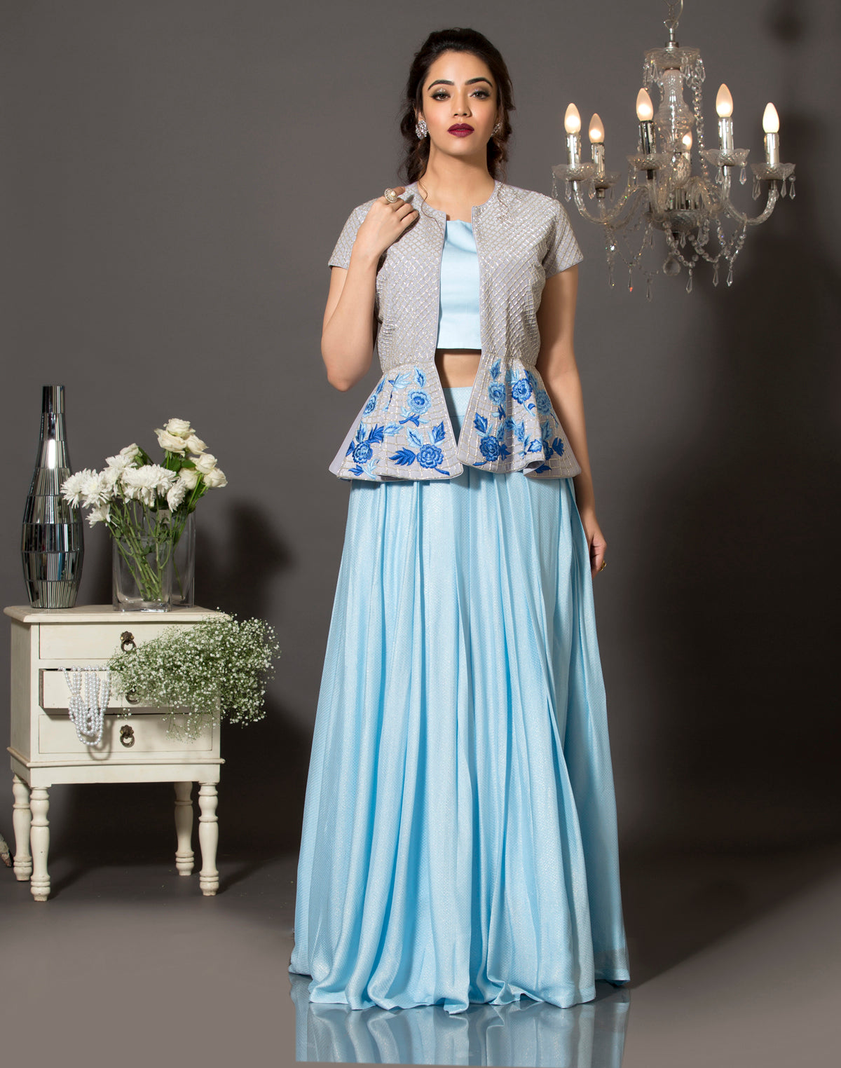 A sky blue shimmer lehenga set with pure crepe grey peplum jacket. The jacket is highlighted using silver cut-dana and the bottom with handcrafted resham embroidery.