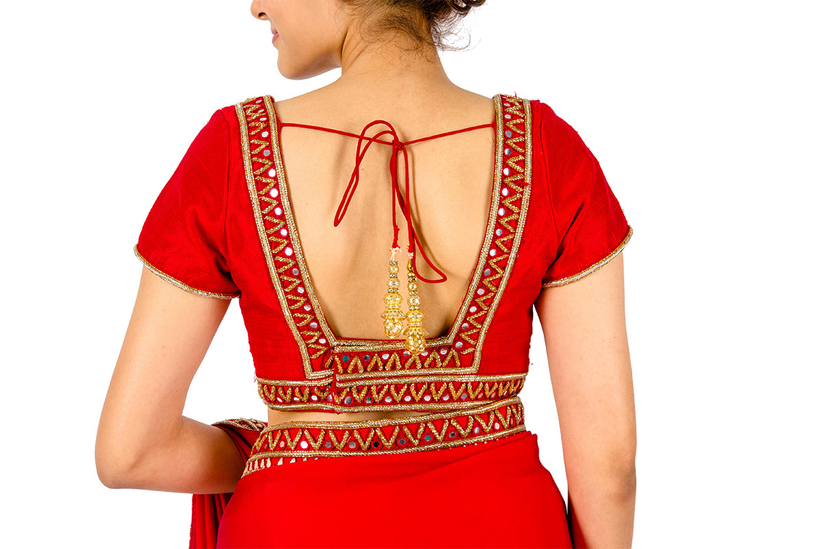 Red Raw Silk Blouse With Mirror Work On Front And A Deep Back is not the usual blouse you'd pair with a saree. This intrinsically designed work has a latkan at the back.