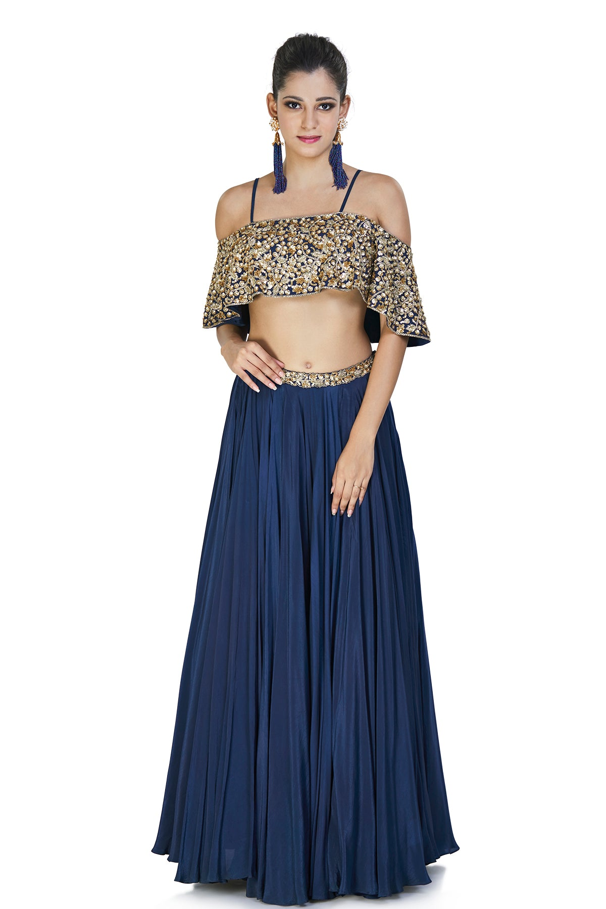 This graceful navy blue ethnic ensemble is finely crafted and comes with a crepe silk skirt with an embellished belly and an off shoulder cape style blouse with sequins and spaghetti straps.