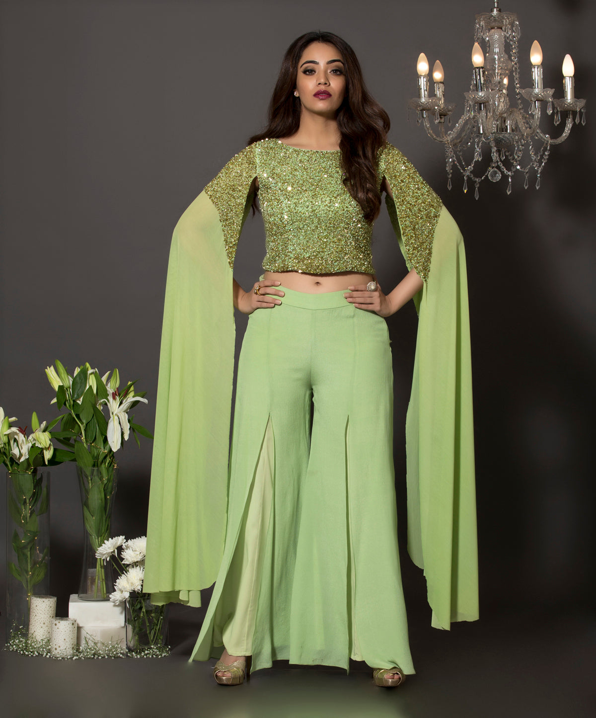Pista green lycra net cape sleeves georgette blouse with pearls and sequins embroidery paired with front slit palazzos made out of pure crepe.