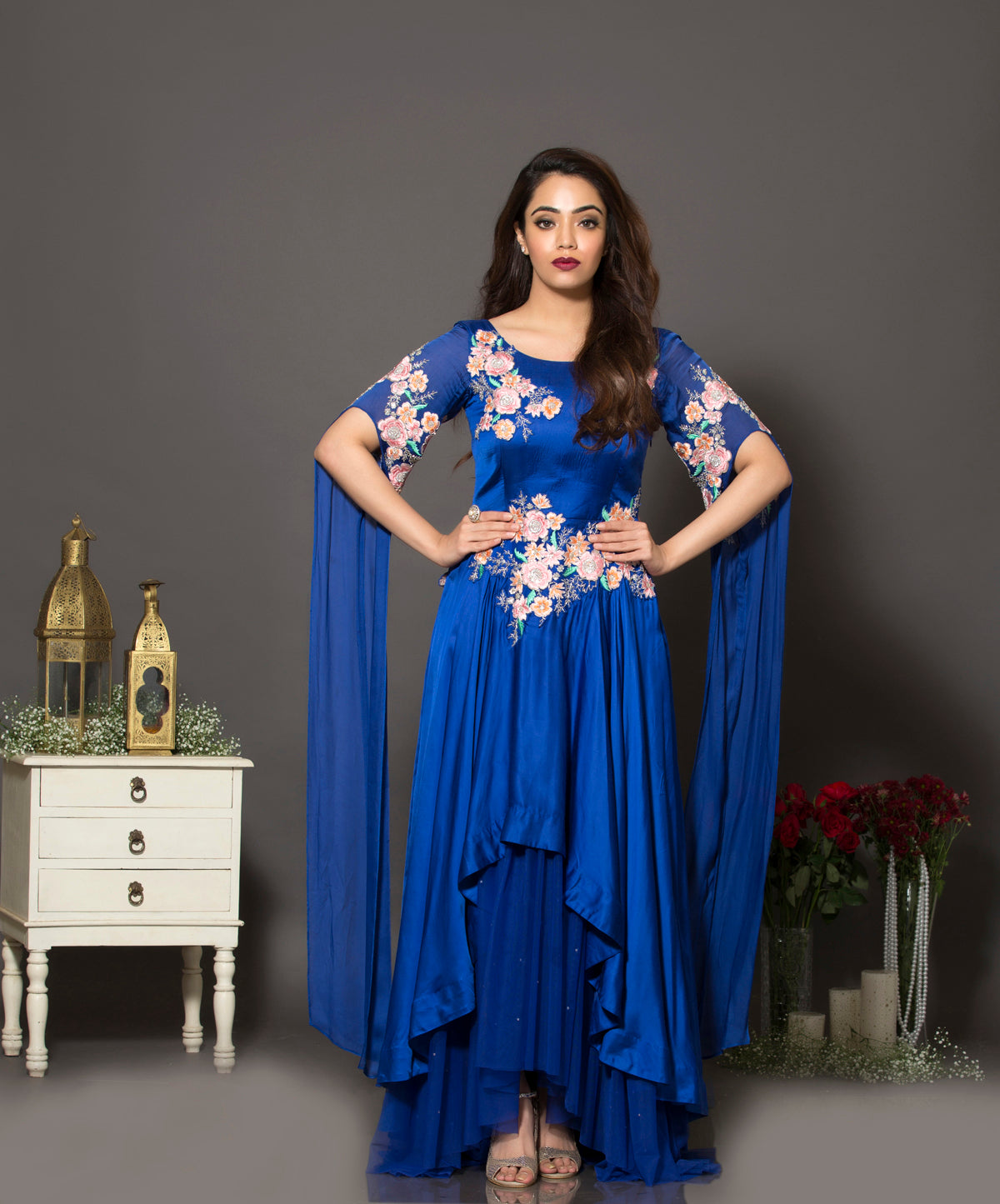 Royal blue cape sleeves layered gown in soft net and satin georgette. The multicolour floral embroidery is highlighted with silver cut-dana and sequins.