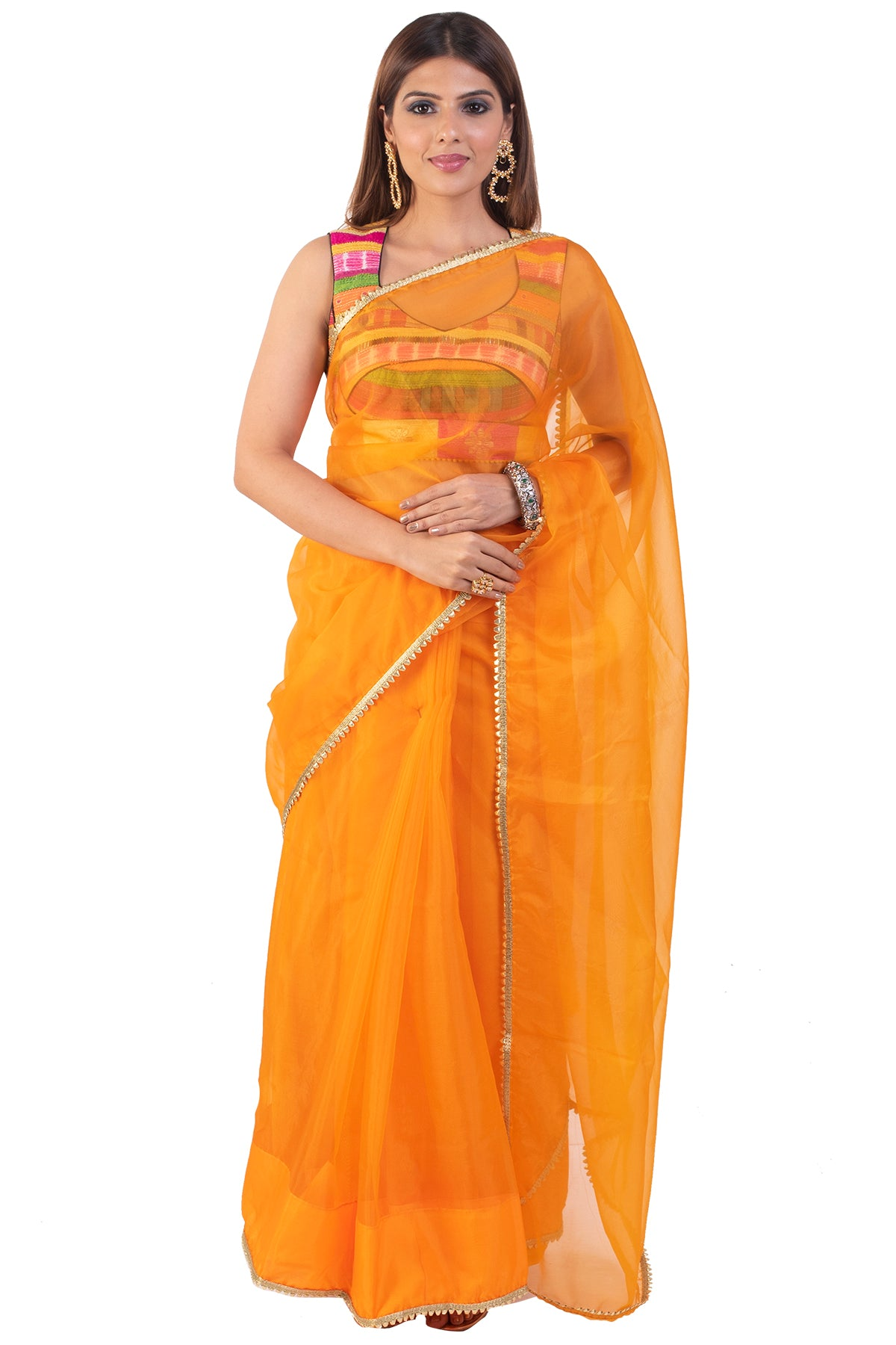 There is nothing more engaging than colors, the sleeveless blouse that is an amalgamation of a range of colors paired with a plain orange saree is the elephant in the room!