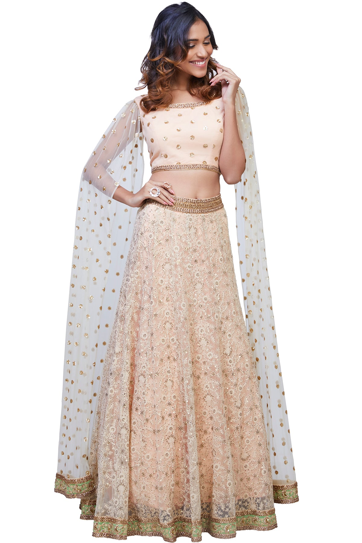 Flutter with finesse in this peach and white net lehenga with thread and sequins embroidery paired with a floor-length cape sleeves blouse.
