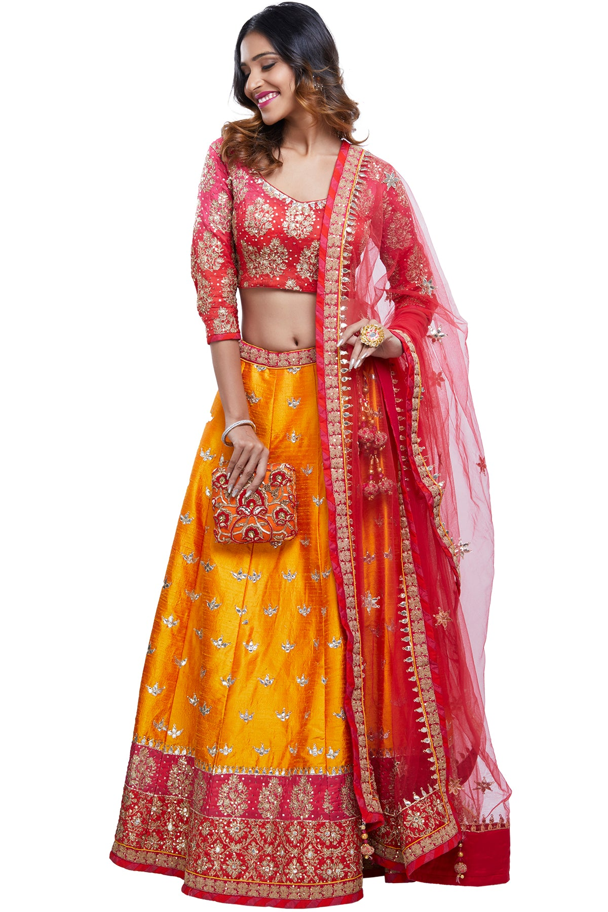 Fall in love all over again with the intricacy, craftsmanship and undeniable elegance that forms this piece. It comes with a shaded coral to hot pink silk blouse & net dupatta with gota embroidery over a rich saffron-hued embroidered lehenga.