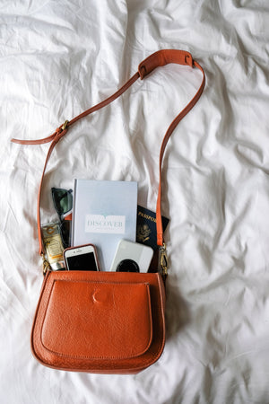 Discover travel journal and other travel items in a purse.