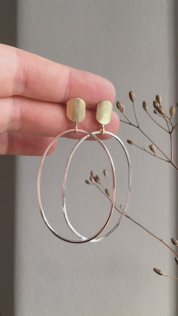 Silver hoops dangling with brass touch on the lobe