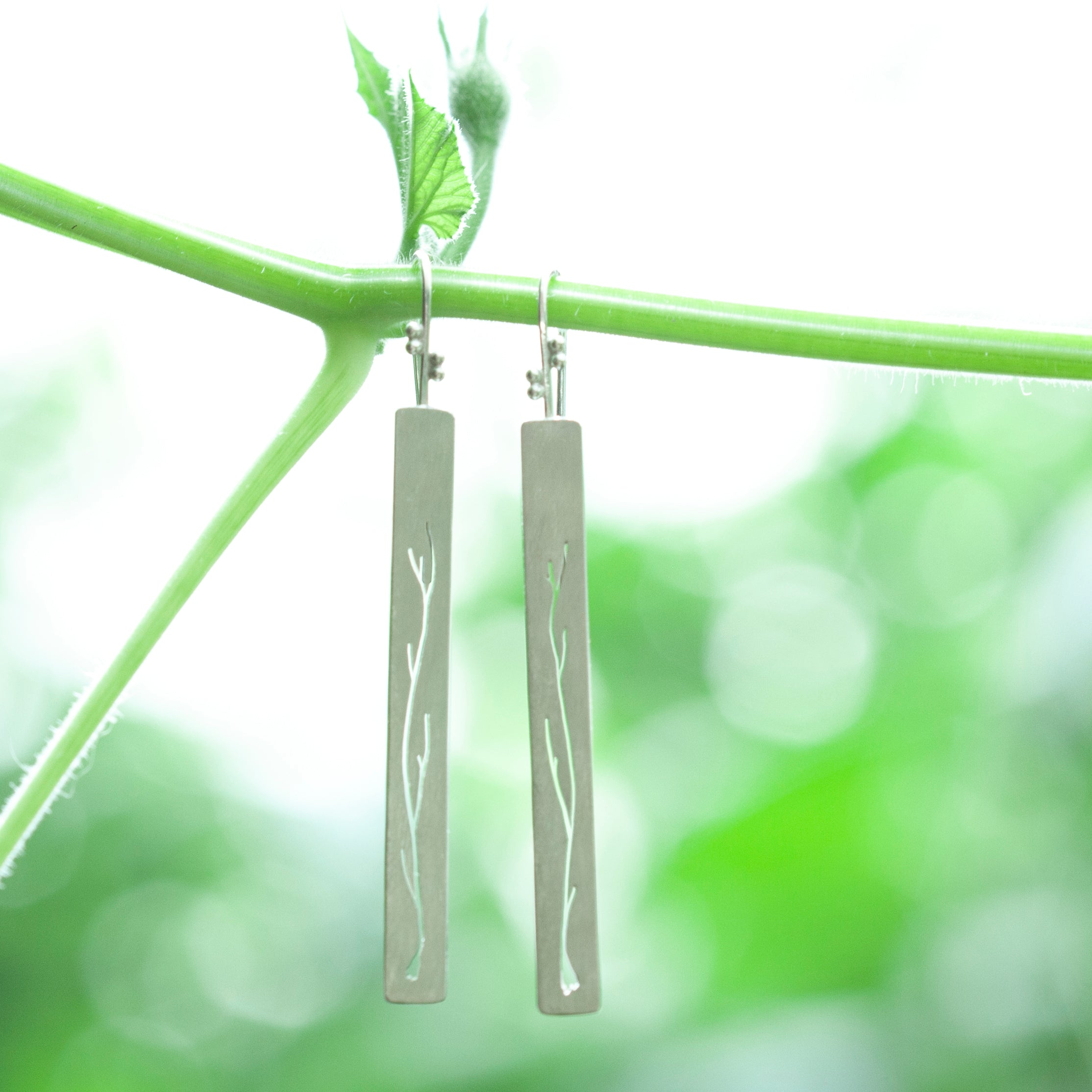 Long silver earrings with branch cut out