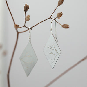 Dangling earrings in silver with cut out branch