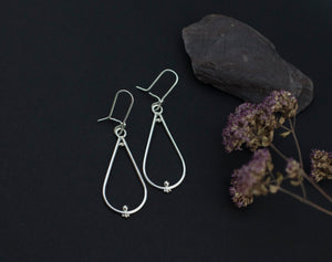 Dangling silver earrings in a teardrop shape