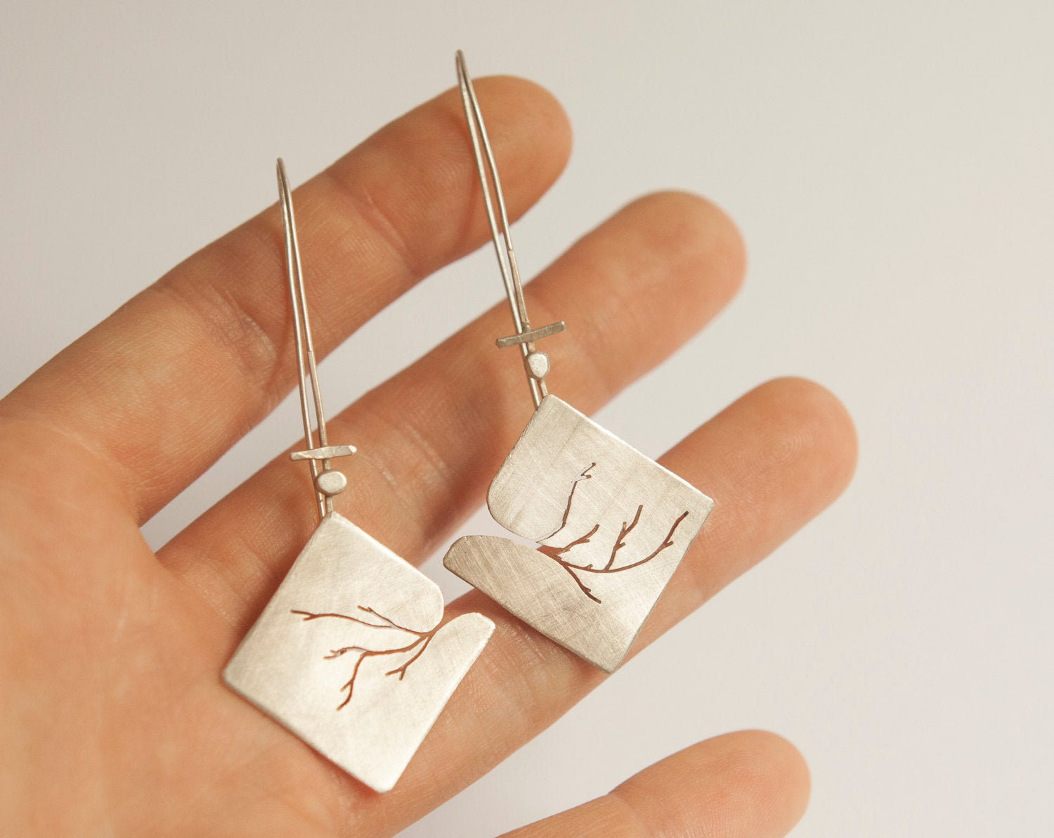 Extra long silver earrings with branch cut out