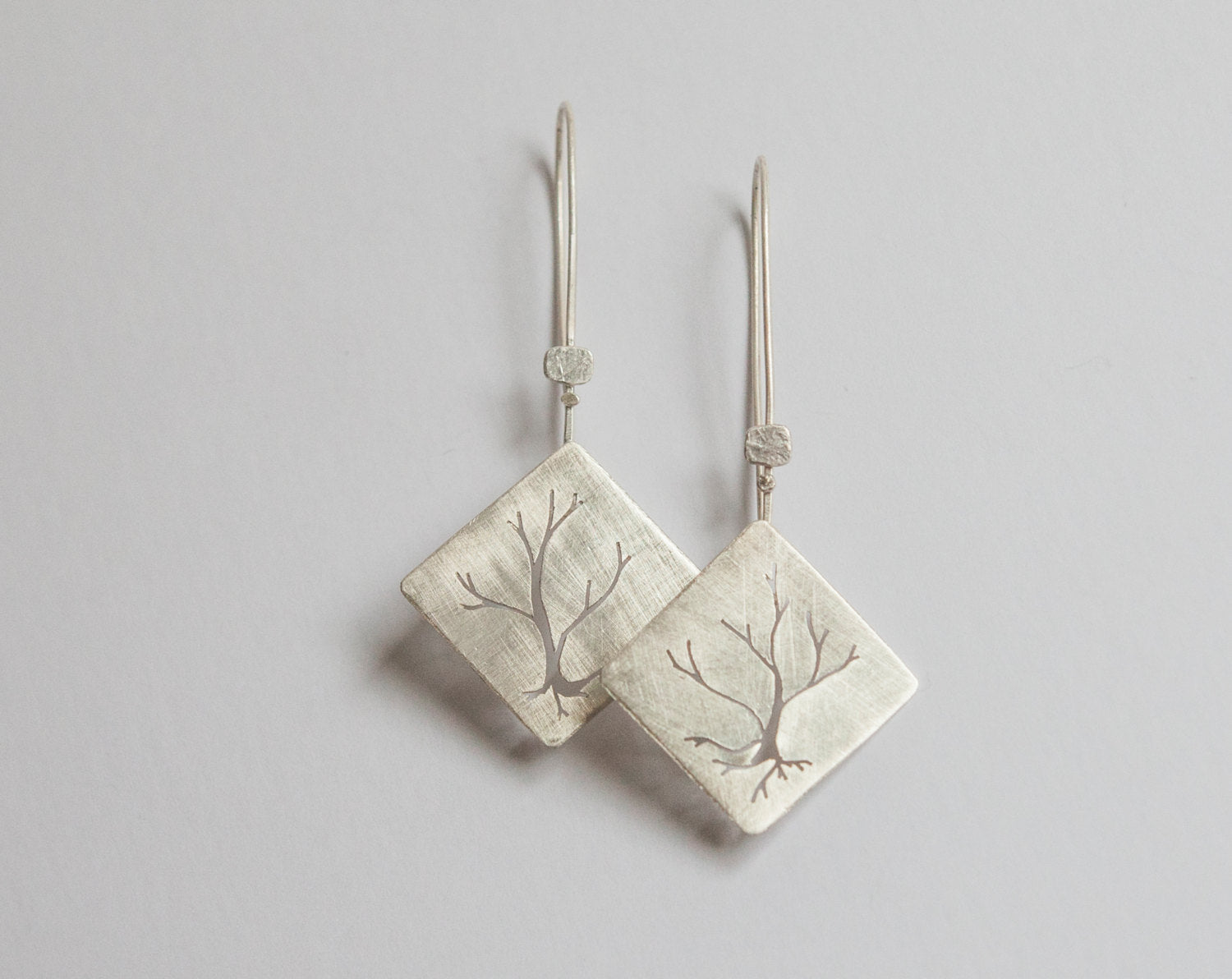 Dangling earrings in silver with tree cut out