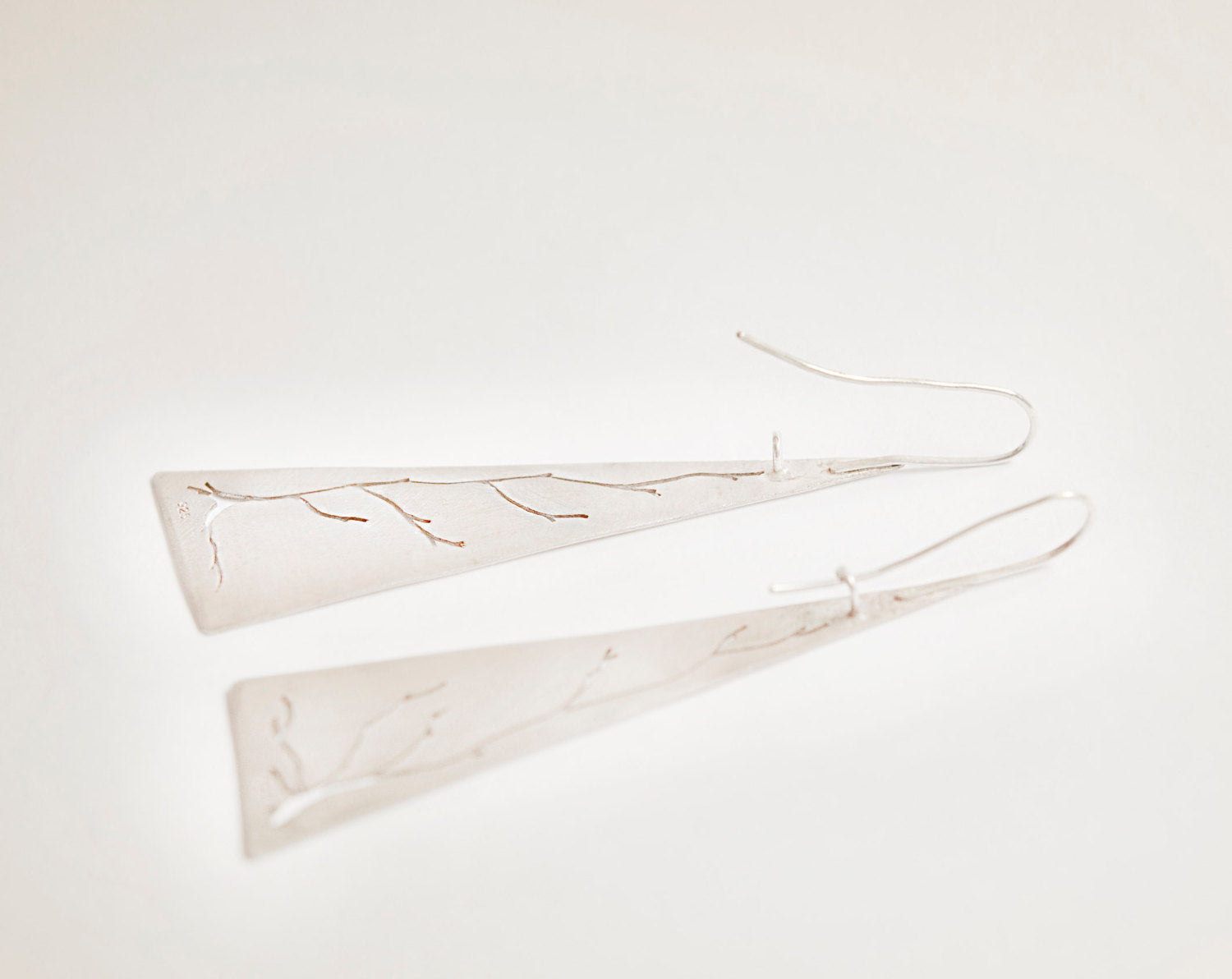 Long triangle earrings in silver with cut out tree