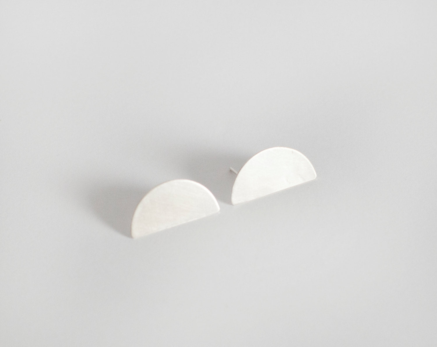 Short halfmoon stud earrings in silver, modern, discreet, stylish, extremely easy to wear •