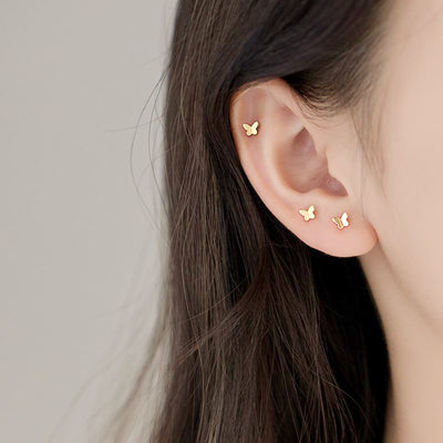Woman Wearing Multi Tiny Dainty Mini Butterfly Minimalist Stud Earrings In 18K Gold Plated 925 Sterling Silver