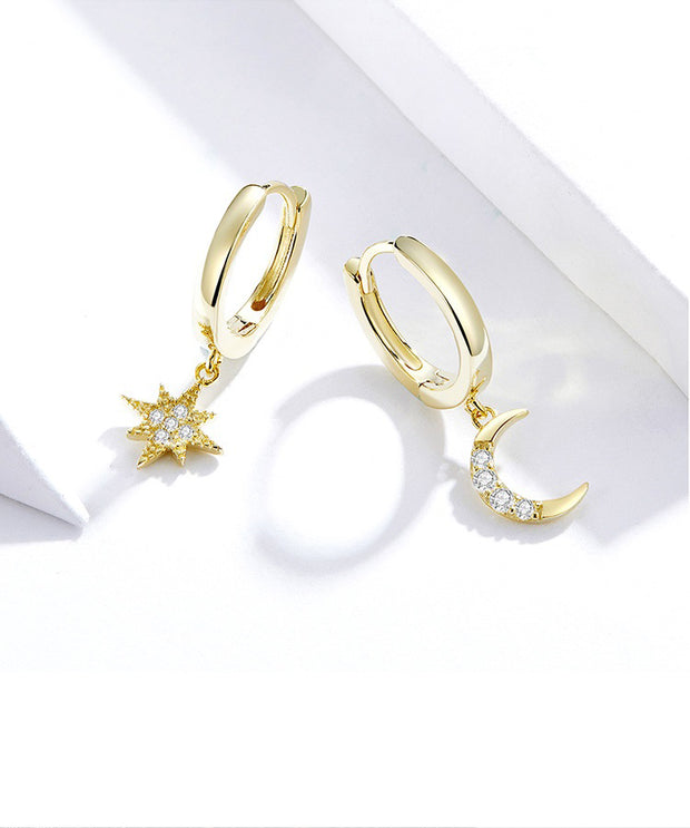 gold plated moon and star earrings set on table